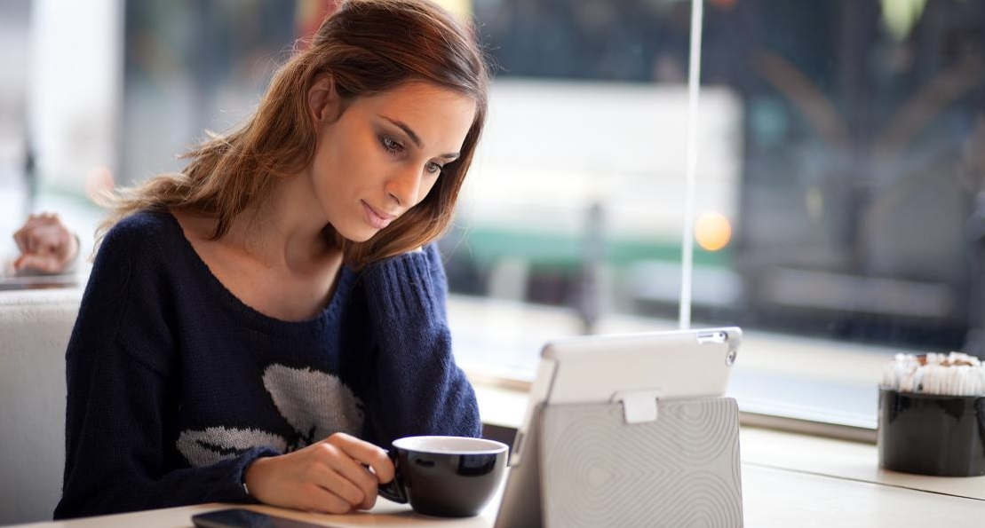 Candid image of a young woman drinking tea / coffee and using tablet computer